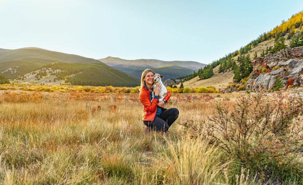 a human holding a small dog while in a grassy area with trees and mountains in the background, Colorado outdoor dog photography, Colorado adventure pups, Serving Denver, Colorado Springs, Fort Collins, and all Colorado pups; Adventure Pup Photography